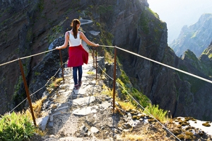 Young girl on the winding mountain trekking path at Pico do Aree