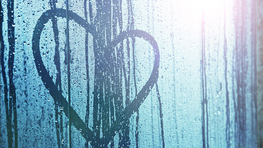 Heart drawn on rainy-streaked window
