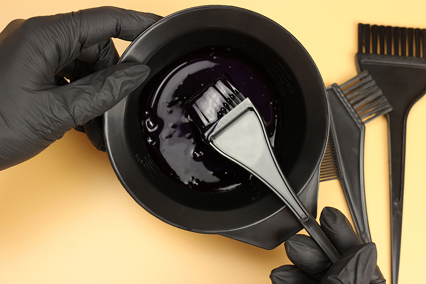 Girl in black gloves mixes hair dye in a bowl